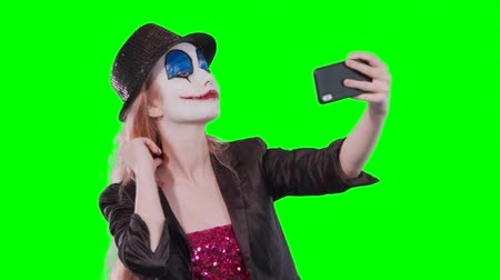 маскарад : Portrait of a happy cheerful blonde woman in halloween clown make-up taking a selfie with mobile phone isolated over green background Стоковые видеозаписи
