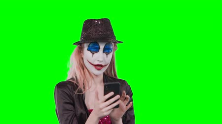 продвигать : Portrait of a happy cheerful blonde woman in halloween clown make-up using mobile phone isolated over green background Стоковые видеозаписи