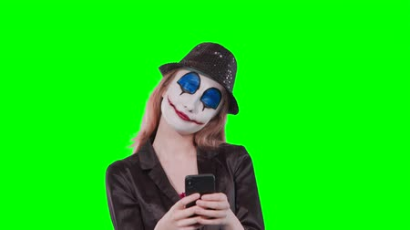 маскарад : Portrait of a happy cheerful blonde woman in halloween clown make-up using mobile phone isolated over green background Стоковые видеозаписи