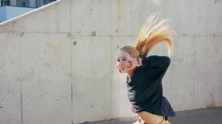 A young girl performs modern hip hop dance on the streets of the city during the summer, twisting and rotating. Stok Video