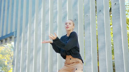 hiphop : A young girl performs modern hip hop dance on the streets of the city during the summer, twisting and rotating. Stock Footage
