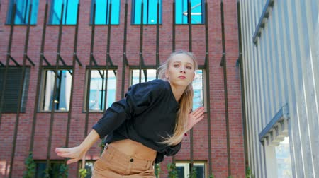 A young girl performs modern hip hop dance on the streets of the city during the summer, twisting and rotating. Wideo