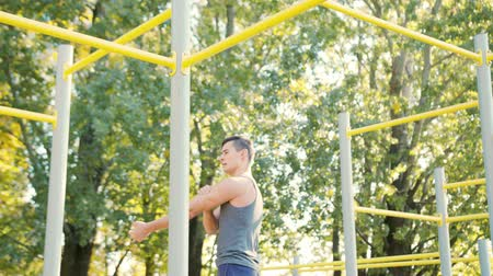 contra : a small athlete resting after exercise Pull-up strength training exercise. Slim athlete a very fit guy fitness instructor or a personal trainer working out his arm muscles on outdoor Stock Footage