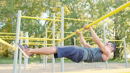 Handsome muscular man doing exercises on horizontal bar outdoors. Calisthenics workout. Slim athlete a very fit guy fitness instructor or a personal trainer working out his arm muscles on outdoor Stok Video