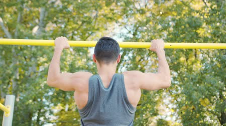 Young muscular man doing pull up exercise on horizontal bar. Slim athlete a very fit guy fitness instructor or a personal trainer working out his arm muscles on outdoor gym as part crossfit workout. Stok Video