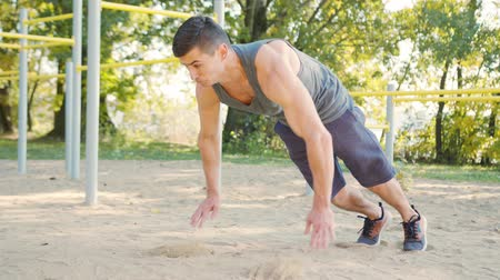 Push-ups strength training exercise. Slim athlete a very fit guy fitness instructor or a personal trainer working out his arm muscles on outdoor beach gym as part of a crossfit workout. Stok Video