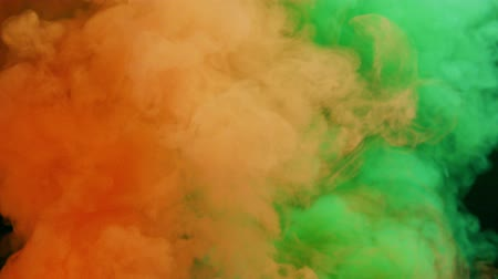 orange and green bomb smoke on black background Stok Video