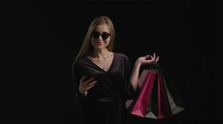 segunda feira : Woman using phone purchase in cool sunglasses and black dress, holding black shopping bag isolated on dark background in black friday holiday or christmas