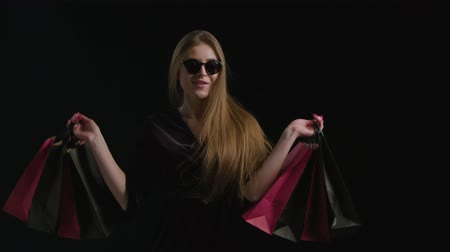 monção : Woman in cool sunglasses and black dress, holding black shopping bag isolated on dark background in black friday holiday or christmas Stock Footage