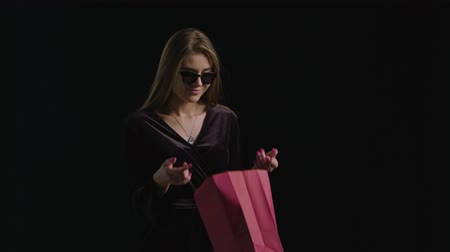 péntek : Happy woman open red bag on dark background in black friday holiday Stock mozgókép