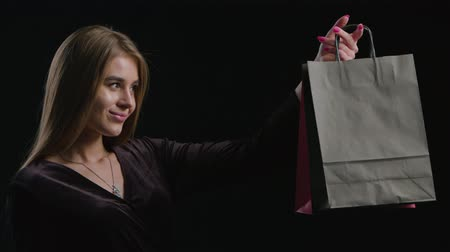 pitka : Sale. Young smiling woman showing shopping bag in black friday holiday. Girl on dark background with copy space