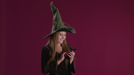 witchcraft : Woman using halloween purchase presents on smartphone, holding phone on dark background
