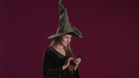 czary : Woman using halloween purchase presents on smartphone, holding phone on dark background