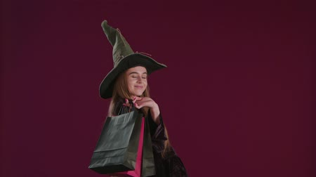 feiticeiro : Girl in Halloween witch costume with shopping bags. Holiday celebration. Happy Halloween shopping. Ggirl in witch hat. Shopping center. Halloween sales. Discount, sale, Autumn sales Stock Footage