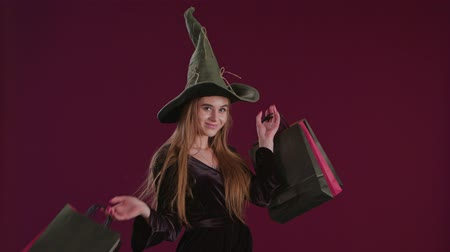 czary : Girl in Halloween witch costume with shopping bags. Holiday celebration. Happy Halloween shopping. Ggirl in witch hat. Shopping center. Halloween sales. Discount, sale, Autumn sales Wideo