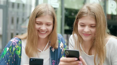 mms : Attractive young ladies using their phones in town. Medium shot. Soft focus Stock Footage