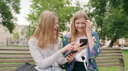 mms : Attractive young ladies sitting on the bench and using a phone in town. Medium shot Stock Footage