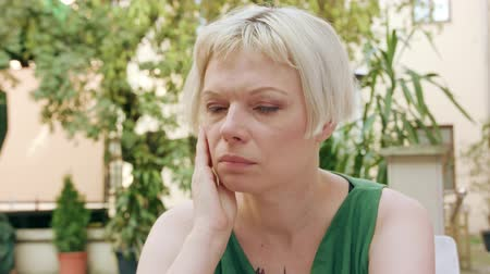 beatiful : A pretty young blonde woman wearing a green dress sitting outside with a worried look on her face. Close-up shot Stock Footage