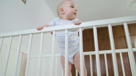 крошечный : Cute baby standing in her crib at home. Close-up shot