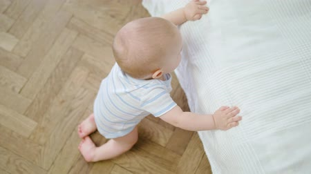 babygirl : Cute baby girl standing on the floor near the bed at home. Close-up shot