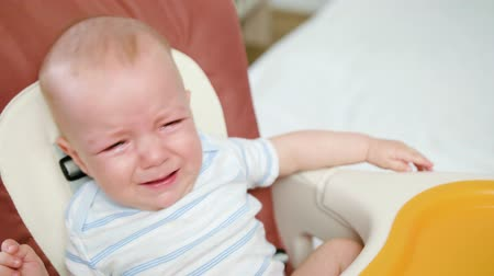 отпрыск : Cute baby crying in the babychair at home. Close-up shot