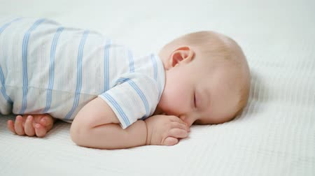 крошечный : Cute baby sleeping on the bed at home. Close-up shot