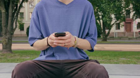mms : An attractive young man sitting and using a phone in town. Close-up shot. Soft focus Stock Footage