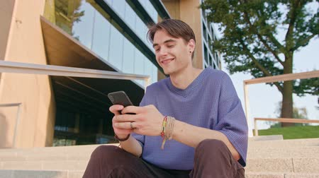mms : An attractive young man sitting and using a phone in town. Medium shot. Soft focus Stock Footage