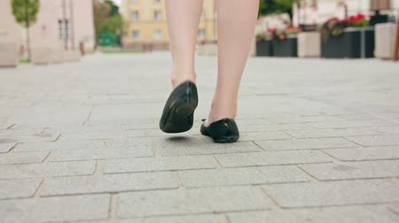 delgado : A close-up on a ladys feet walking in town. Close-up dolly shot. Soft focus