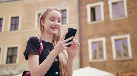 mms : An attractive young red-haired lady using a phone in town. Close-up shot. Soft focus Stock Footage