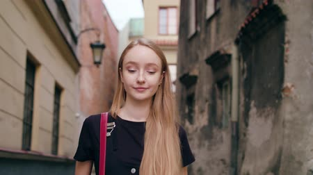 mms : An attractive young red-haired lady walking and holding a phone in town. Medium dolly shot. Soft focus Stock Footage