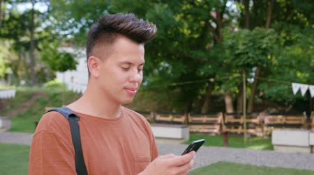 orange t shirt : An attractive young man wearing an orange T-shirt walking and using a phone in town. Close-up dolly shot. Soft focus Stock Footage