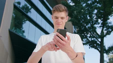 mms : An attractive young man wearing a white T-shirt using a phone in town. Medium shot. Soft focus Stock Footage