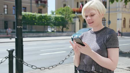 mms : An attractive young blonde lady using a phone in town. Medium dolly shot. Soft focus