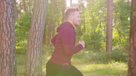 perspiration : A young man running in the forest. Medium shot. Lens flare Stock Footage