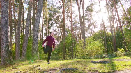 cardio workout : A young man stretching in the forest. Long shot Stock Footage