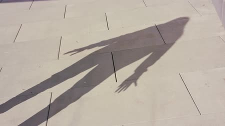 рэп : A young womans shadow dancing outside. Medium shot