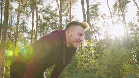 perspiration : A young man stretching in the forest. Medium shot. Lens flare Stock Footage