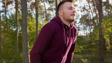 perspiration : A young man stretching in the forest. Medium shot to close-up. Stock Footage