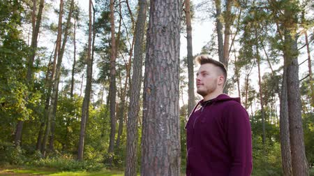 perspiration : A young man walking in the forest. Medium shot Stock Footage