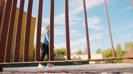 rapper : A young woman dancing outside behind the fence. Long shot