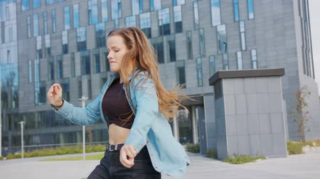 рэп : A young woman dancing outside. Medium shot