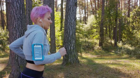 браслет : A young women with pink hair jogging in the forest. Medium shot Стоковые видеозаписи