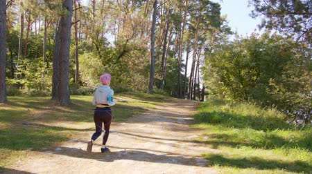 bilezik : A young y with pink hair jogging in the forest. Long shot Stok Video