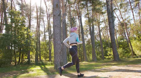 браслет : A young women with pink hair jogging in the forest. Long shot