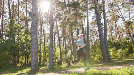 браслет : A young y with pink hair jogging in the forest. Long shot Стоковые видеозаписи