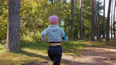 браслет : A young y with pink hair jogging in the forest. Medium shot Стоковые видеозаписи