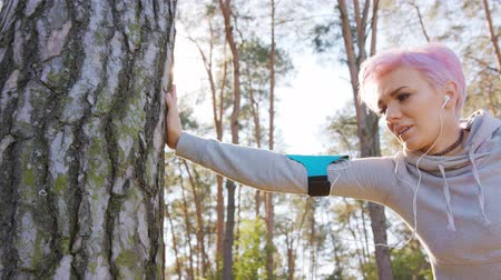 hajló : A young y with pink hair Leaning against a tree in the forest. Close-up shot Stock mozgókép