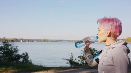 outskirts : A young y with pink hair drinks water after jogging at the lake. Medium shot