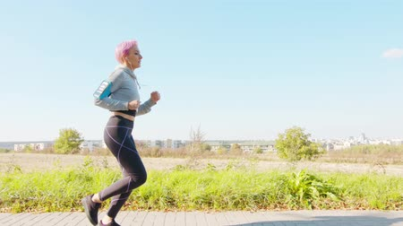 bracciale : A young women with pink hair jogging in the suburbs. Long shot